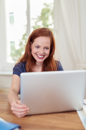 reacting: Young attractive businesswoman smiling as she reads the screen on her laptop reacting with delight to good news