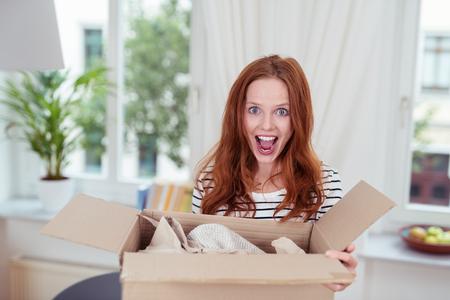 Aufgeregte junge Frau mit einem in einem Karton geöffnet Paket mit ihrem Mund offen stehen in Freude und Überraschung, drinnen zu Hause