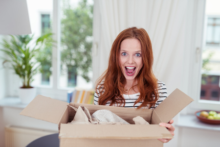 carton: Excited young woman with an opened package in a cardboard box standing with her mouth open in delight and surprise, indoors at home