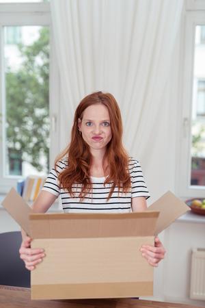 cajas de carton: Mujer rubia joven con la cara divertida dentro de su casa, Llevar una caja de cartón abierta mientras mira a la cámara