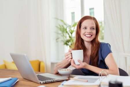 master: Thoughtful Young Woman Having her Breakfast at her Home Office, Showing Happy Facial Expression.