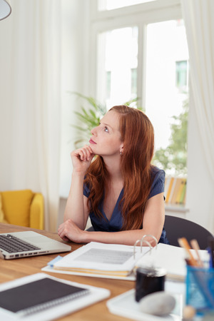 working at home: Young business woman sitting in an office at a desk daydreaming and staring up into the sky with a serious faraway expression