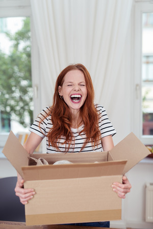 delivery box: Attractive young woman enjoying a hearty laugh as she holds an opened brown cardboard box with packaging in her hands in her living room