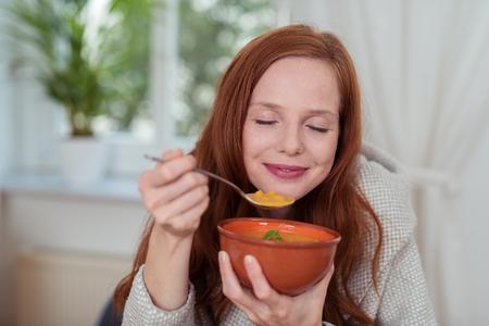 눈 닫고 행복한 표정으로 집에서 사려 깊은 젊은 여자 먹는 건강한 수프를 닫습니다. 스톡 콘텐츠