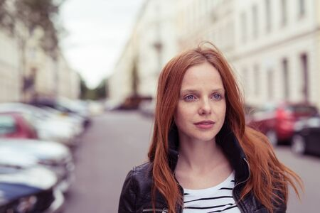 red hair girl: Close up Pretty Blond Young Woman Walking at the Street While Looking Into the Distance with Serious Facial Expression. Stock Photo