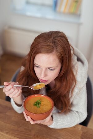 High Angle View of a Thoughtful Pretty Young Woman Eating Soup on a Bowl at the Wooden Table While Looking Into the Distance.