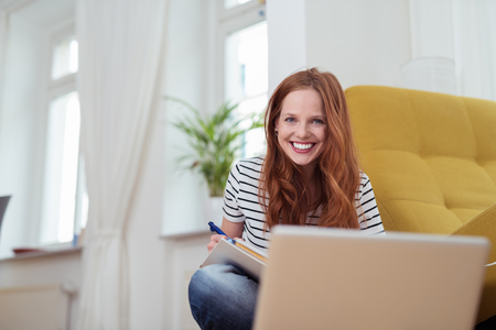 girl studying: Attractive Young Woman Smiling at the Camera While Doing her Homework at the Living Room. Stock Photo