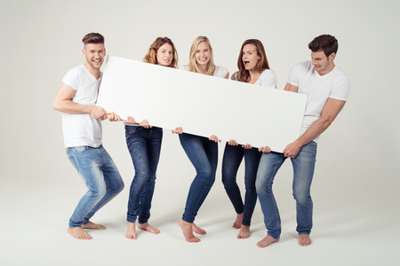 Five Young Friends Holding Rectangular White Board Together with Copy Space in Horizontal Orientation Against White Wall Background. Stock Photo - 45069134
