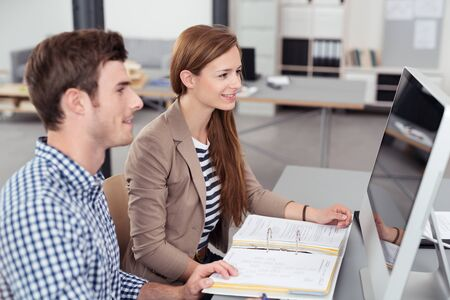 verifying: Two Young Businesspeople Looking at the Computer Screen Together While Verifying Some Notes Inside the Office Stock Photo