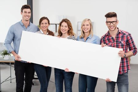 happy workers: Happy Young Office Workers in Casual Outfits, Holding a Plain White Rectangular Poster with Copy Space and Smiling at the Camera.