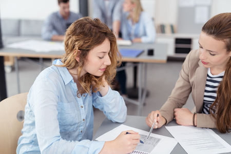 people sitting: Two Young Attractive Office Women Discussing the Content of a Document on Top of the Table Inside the Office. Stock Photo