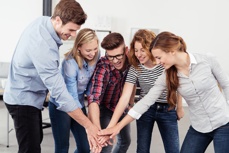 all in one: Five Young Businesspeople Putting Hands Together All for One Inside the Office for Teamwork Concept.