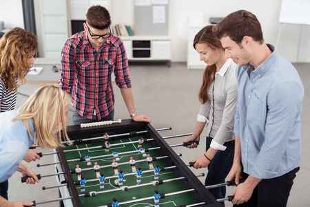 kickoff: Five Young Workmates Enjoying Table Soccer Game Inside the Office During their Break Time. Stock Photo