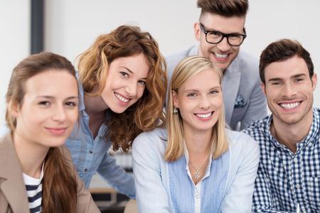 jovenes: Close up Grupo de los Cinco alegres jóvenes profesionales dentro de la oficina, sonríe en la cámara