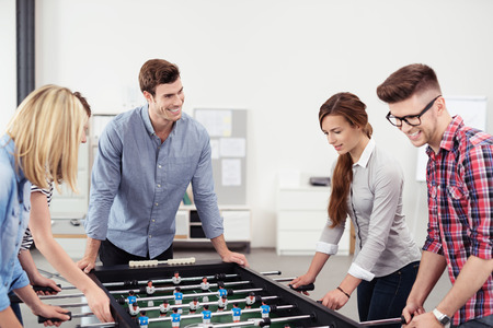 workmates: Five Happy Young Workmates Playing Table Soccer Game Inside the Office During their Break Time.