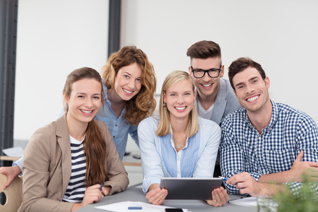 formations: Five Young Office Workers in Casual Clothing, Sitting Inside the Boardroom, Smiling at the Camera.