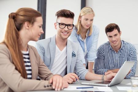administracion de empresas: Apuesto hombre de negocios joven que sonríe a la cámara mientras en una reunión de negocios dentro de la sala de juntas.