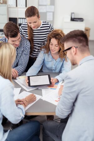 teamwork business: Five Young Office People Looking at the Tablet Screen with Copy Space Together While Having a Meeting Inside the Boardroom.