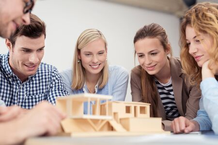 administrative buildings: Five Young Designers Checking The Details of a Wooden Home Miniature on Top of the Table.