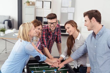workmates: Five Young Workmates Putting their Hands on Top of One Another Over Soccer Table Inside the Office.