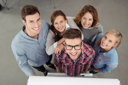 business administration: Five Cheerful Young Workmates Smiling at the Camera from High Angle View Inside the Office.