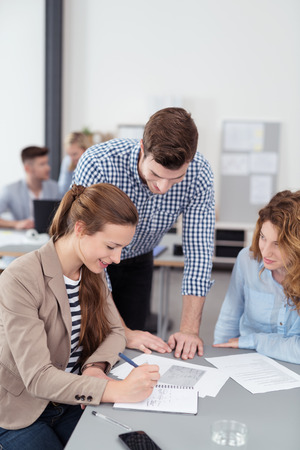 businesspeople: Three Young Businesspeople Talking About the Content of a Document on Top of the Table Inside the Office. Stock Photo
