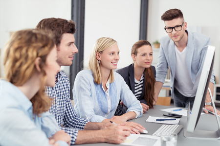 formations: Five Young Office Workers Reading Something on Computer Together While Having a Business Meeting. Stock Photo