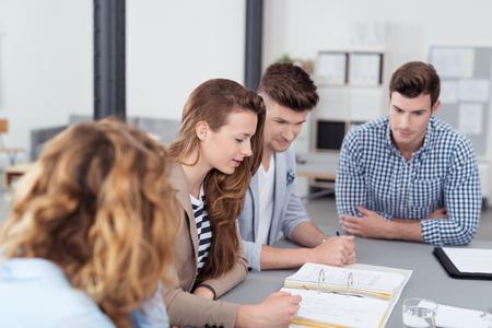 Jóvenes trabajadores de oficina en una reunión dentro de la oficina, la revisión de los documentos recopilados en la tabla de arriba Foto de archivo - 45069394