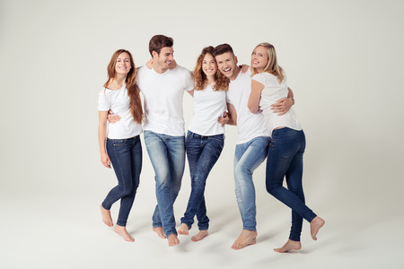 Group of Five Happy Young Close Friends in Casual Plain White Shirt and Jeans Against White Background. Stock Photo