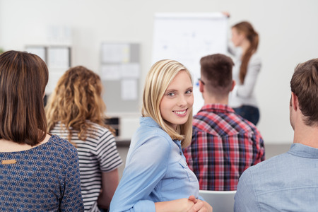 会議中のオフィスで、カメラを背中から見てかなり若い女性を笑顔します。