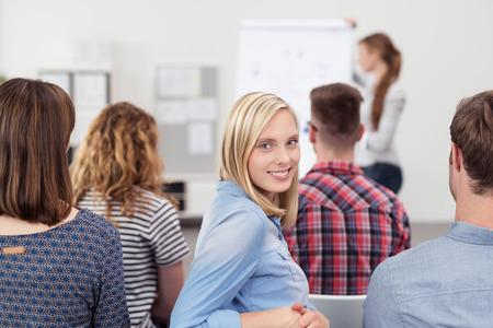 Sorridente abbastanza giovane donna in un incontro all'interno dell'ufficio, guardando la telecamera dalla schiena. Archivio Fotografico