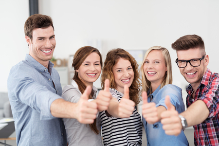 hand signs: Half Body Shot of Five Happy Young Office Workers Showing Thumbs Up Hand Signs and Smiling at the Camera.