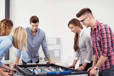 Five Young Workmates Playing Table Soccer Game Seriously in the Office During Free Time.