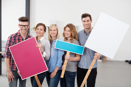formations: Five Happy Young Employees Holding Three Placards with Copy Space for Texts and Looking at the Camera.