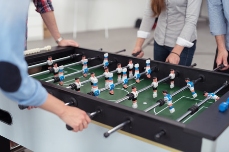 kickoff: Group of Male and Female Office Workers Playing Table Soccer Game During their Break Time to Relieve Work Stress.