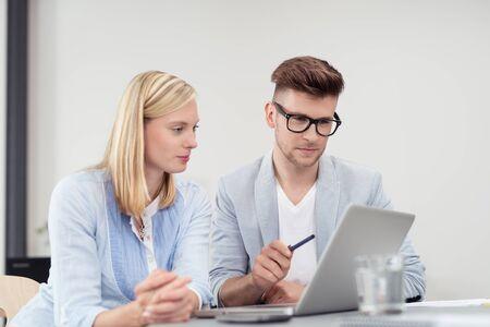 Jeune couple d'affaires en train de lire quelque chose sur un ordinateur portable au bureau. Banque d'images - 45069427