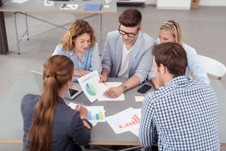 High Angle View of Five Young Office People Brainstorming for Ideas Using Printed Charts Inside the Boardroom.