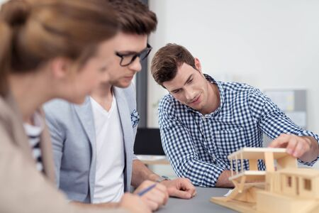 young engineer: Young Professional Architects Having a Brainstorming Meeting at the Table Using a Wooden House Miniature Template.