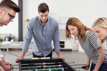 social actions: Handsome Young Man Watching his Colleagues Playing Table Soccer Game Inside the Office Stock Photo