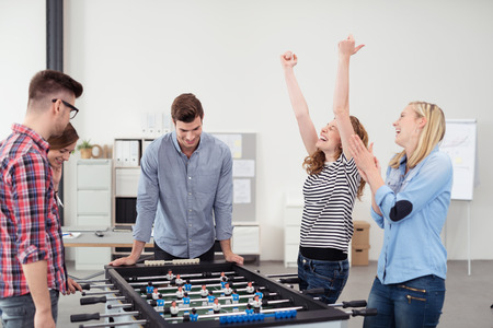 Group of Young Office Workers Enjoying Table Soccer Game Inside the Office During their Break time. Stock Photo
