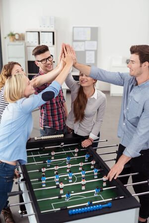 workmates: Five Happy Young Workmates Putting Their Hands in the Air Together Over a Soccer Table Inside the Office.