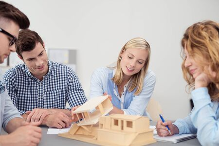 architectural firm: Designers or partners in an architectural firm working together on a wooden model house as they sit grouped around a table together Stock Photo