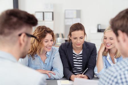 Fünf junge Büro Menschen Brainstorming für Ideen auf der Tabelle in der Vorstandsetage. Standard-Bild