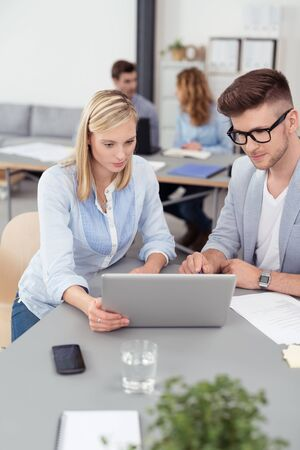 consulting room: Two Young Businesspeople Reading Something at the Laptop Computer Together While Having a One-on-One Business Meeting.