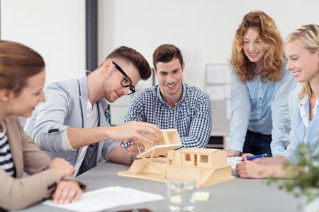 arquitecto: Cinco J�venes Arquitectos de lluvia de ideas para el nuevo hogar ideas utilizando una miniatura dentro de la oficina.