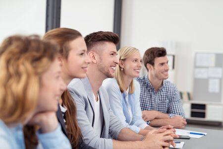 personas escuchando: Jóvenes de oficina con expresiones faciales felices escuchando a alguien Discutiendo con ellos dentro de la oficina