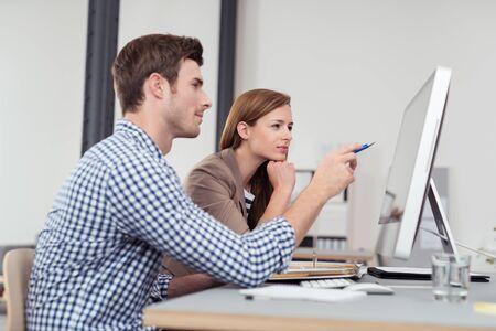 administracion de empresas: Dos empresarios jóvenes sentados a la mesa y mirando a las figuras en la pantalla del ordenador Foto de archivo