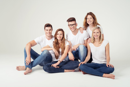 young group: Group of Five Happy Young Friends In Casual Plain White Shirts and Jeans, Smiling at the Camera While Sitting on the Floor Against Off-White Background Inside the Studio. Stock Photo