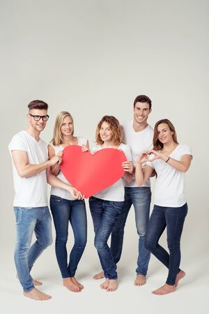 community people: Group of Young Friends in Casual White Shirts and Jeans, Holding a Big Red Heart Cutout with Copy Space and Smiling at the Camera Against Off-White Background Inside the Studio.