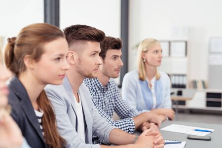 personas escuchando: Empresarios jóvenes sentados en la mesa dentro de la sala de juntas y escuchar a alguien hablar.